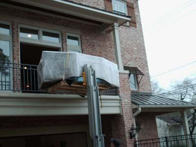 forklift with heavy item on it being placed on second story of a home