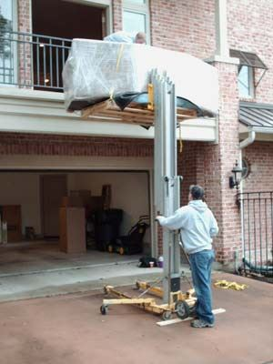 forklift lowering from second floor of a home with heavy item on it