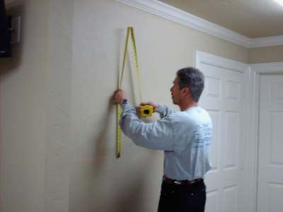 older man measuring a wall to hang an item