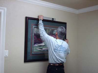 older man checking to see if picture is level on a wall