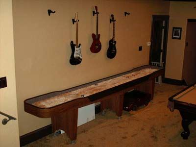 shuffleboard game against a wall with a mounted display of multiple guitars above it